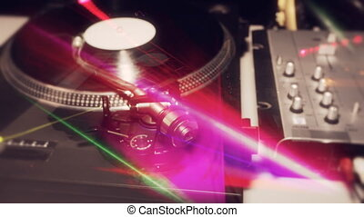 a pan across dj turntables with abstract light patterns overlayed
