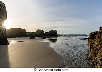 panorama of sandy beach and jagged cliffs in Galicia at sunset