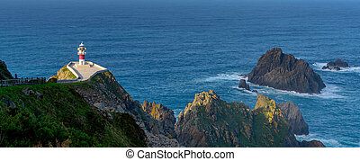 panorama of the Cabo Ortegal lighthouse in Galicia with green cliffs and sunlight and deep blue ocean