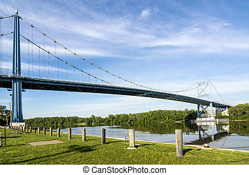 A panoramic view of downtown Toledo Ohio's Anthony Wayne Bridge or High Level bridge that crosses the Maumee river. A beautiful blue sky with white clouds for a backdrop.