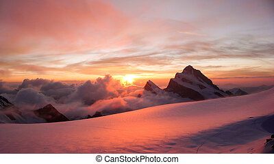 panoramic view of gorgeous pink sunrise over glacier and high mountain peaks in the Alps