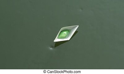 A paper boat floating on the river.