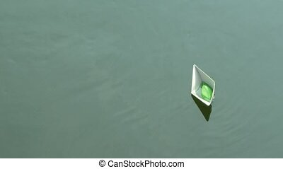 A paper boat floating on the river. - a paper boat floating...