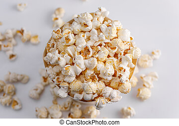 A paper bucket full of popcorn on a white background. Top view.