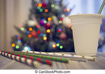 A paper cup and straws on a wooden table against decorated Christmas tree
