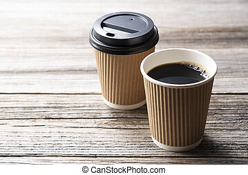 A paper cup of coffee on an old wooden background
