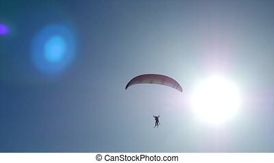 A paraglider flies front of the sun in the blue sky with...