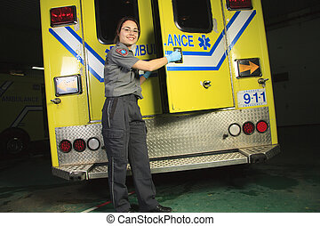 A paramedic, closing the door of the ambulance.