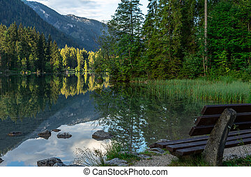 A park bench at a small mountain lake in the sunshine