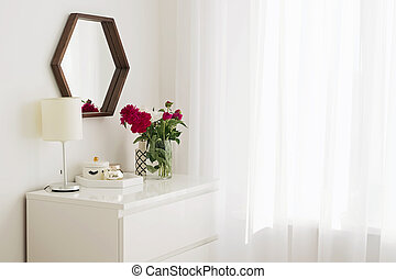 A part of modern bedroom in white colors with bouquet of peonies