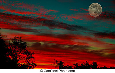 A partially full moon during a beautiful sunset.