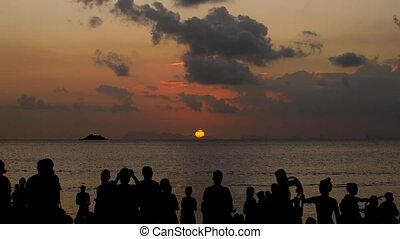 A party on the beach at sunset. Unrecognizable people admire the sunset at sea.