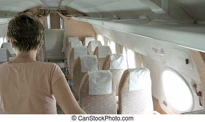 A passenger is walking in the aisle of a plane in a search...