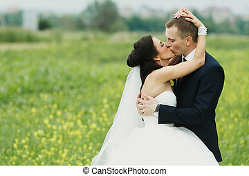 A passion kiss of newlyweds in the open air