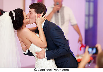 A passionate kiss of just married couple during their first...