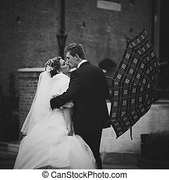 A passionate kiss of young wedding couple kissing in the rain