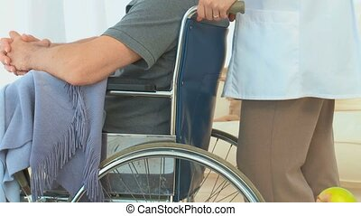 A patient in a wheelchair talking with his nurse