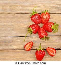 pattern of ripe strawberries on a wooden table. Top view.
