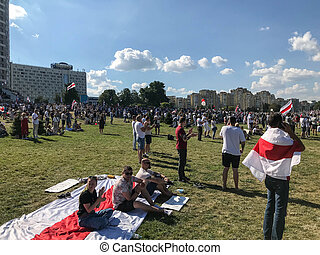 a peaceful rally in the city center near the stella, the memorial complex. men and women sit on a large fabric white-red-white flag, a symbol of independence. Belarus, Minsk, 23 August 2020
