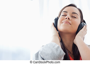 A peaceful woman listening to music on her headphones - A...