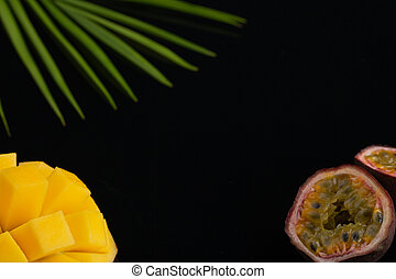 peeled pineapple, bamboo and passion fruit. Fresh Tropical Fruits. On a black background. Top view. Copy space.