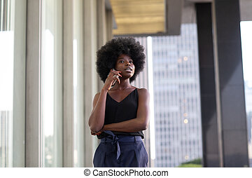 A pensive African american woman talking on a cell phone, city skyscrapers on the background