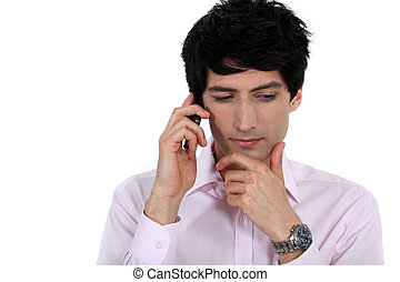 A pensive businessman over the phone.