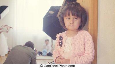 A pensive child standing near the door - A pensive girl...