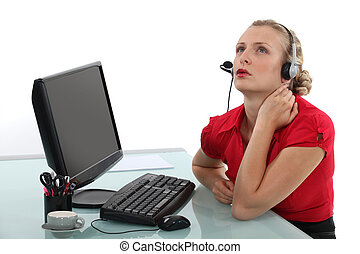 A pensive secretary sitting behind her desk