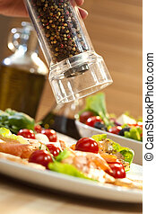 A pepper mill grinding pepper onto a seafood salad of smoked salmon and shrimp or prawns, shot in golden light with olive oil and balsamic vinegar out of focus in the background.