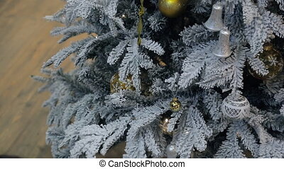 A person decorates the Christmas tree in the room before the...
