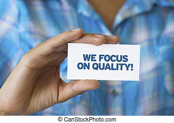 We focus on quality - A person holding a white card with the...