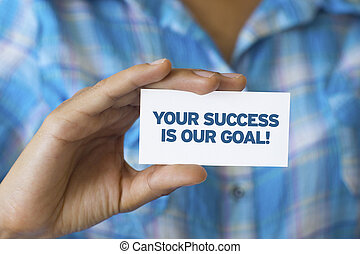 A person holding a white card with the words Your success is our goal