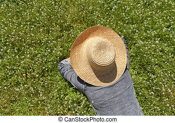 A person in hat lying down on green field with flowers