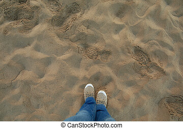 A person in jeans and sneakers stand on sandy beach. Personal perspective used.