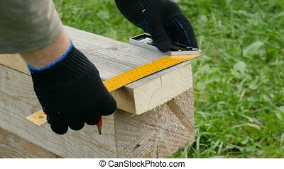A person makes a mark on the board. Saws off a piece from the board with electric jigsaw.