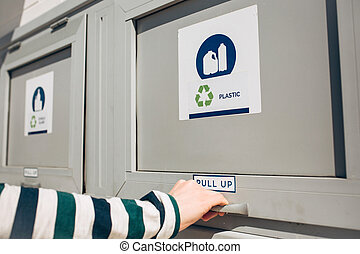 A person opens a modern waste bin - A person opens or closes...