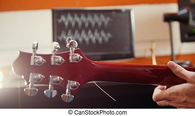 A person playing guitar and recording the sound in the studio. The music wave on the screen