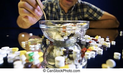 A person sitting in front of a bowl with pills is going to...