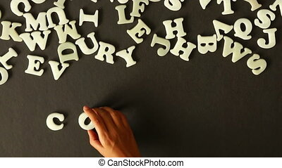 A person spelling Consulting with plastic letters