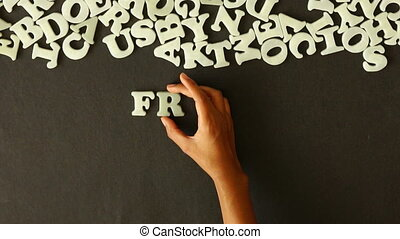 A person spelling Free Estimate with Plastic Letters.