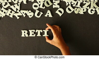 A person spelling Retirement Planning with plastic letters