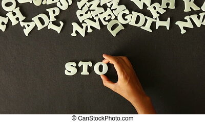 A person spelling Stop Bullying with Plastic letters