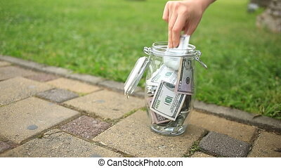 A person takes money from a glass jar on the street. Dollars in a glass jar