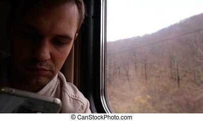 A person uses a smartphone in a compartment of a passenger...