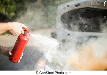 A person who sprays from a fire extinguisher over a vehicle in flame