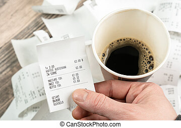 person with a coffee holds a receipt in his hand
