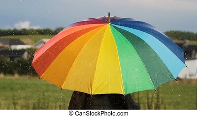 A person with colorful umbrella in the rain