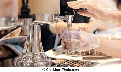 A person working in the buffet. Pouring a drink in the cup...