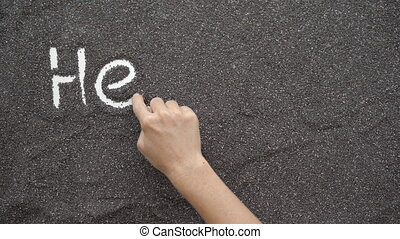 A person writes Health in chia seeds spread on a flat surface.